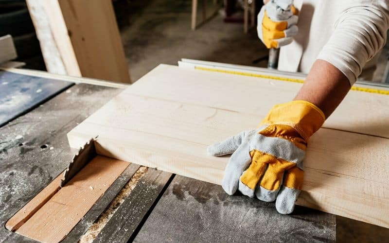 How to choose a hybrid table saw - man cutting wood